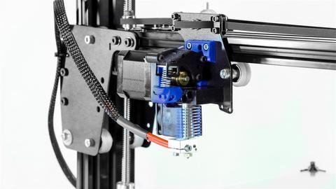The print head runs on aluminum, V-slot linear extrusion profiles through polycarbonate bearing wheels