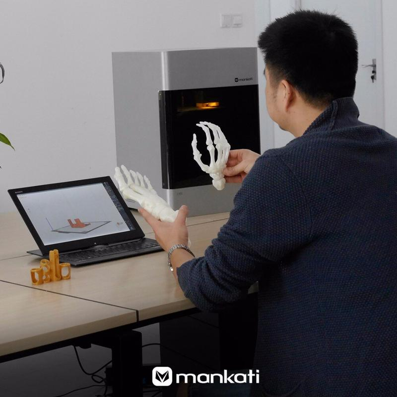 A man prints hands of skeletal on the Mankati E180 3D printer