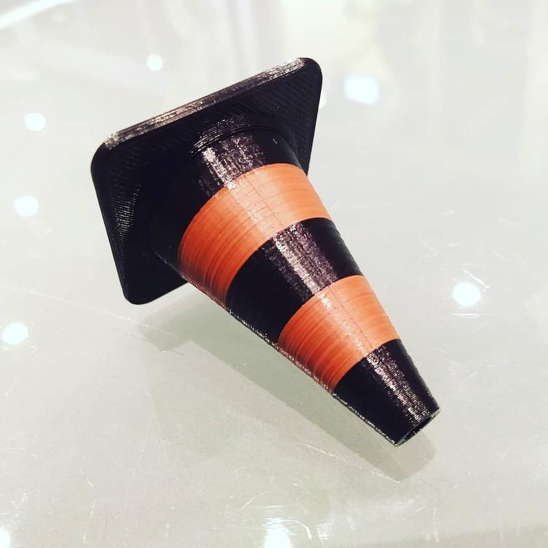 Vertex prints with PLA, ABS and other materials. By installing an additional extruder you will be able to print multi-color or multi-material object, just like this dual-color traffic cone.