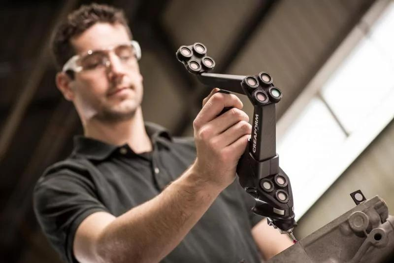 the man holds a handyPROBE 3D scanner in his hand